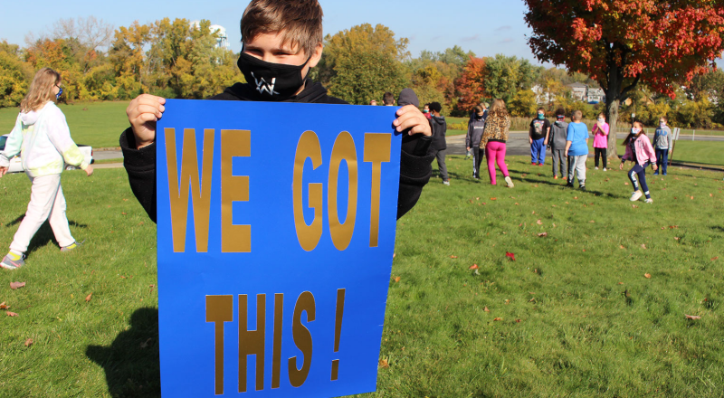 Harmony Hill student holding sign